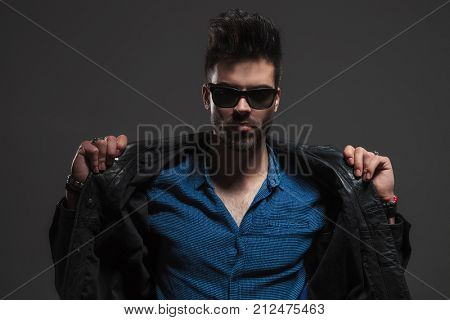 man in sunglasses opening his leather jacket to reveal his chest on grey studio background