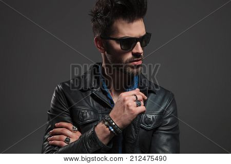 young hot man in leather jacket and sunglasses looking to side on grey background; he is wearing rings on his fingers, bracelet at his wrist