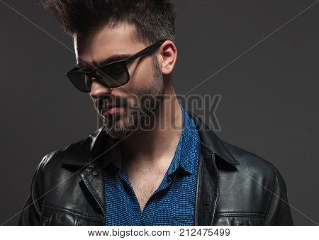 dramatic young man in sunglasses and leather jacket looks to side on grey studio background