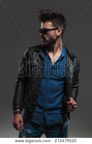 young sexy man in sunglasses and leather jacket holds collar and looks to side