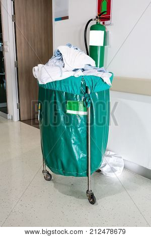 A pile of used clothes in hospital movable trolley with green bag for laundry.