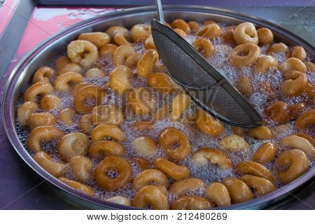"""poster of """"Lokma"""" dessert; Prepared with flour yeast salt and sugar prepared by frying in oil and sweetened with dark-colored syrup."""