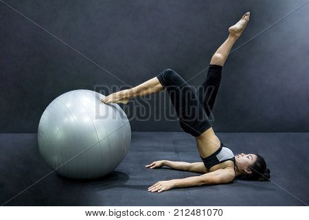 Young Asian athlete woman doing pilates exercises with exercise ball in fitness gym healthy lifestyle concepts