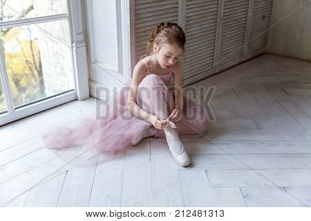 Beautiful young ballerina who puts on pointe shoes at white wooden floor background near the window, with copy space. Ballet practice. Beautiful slim graceful ballet dancer.