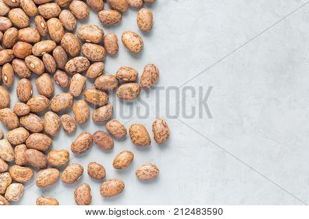 Uncooked dry pinto beans on a gray concrete background top view copy space horizontal