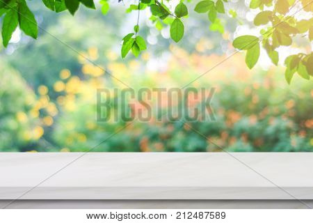 Empty white marble table over blur green nature park background tabletop shelf counter design background for product display montage