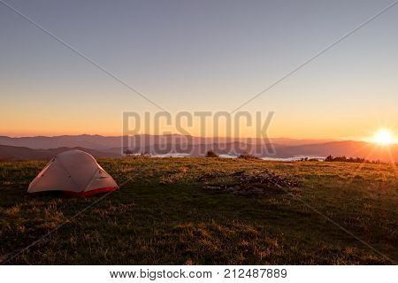 Tent on huckleberry knob overlooking appalachian mountains at sunrise