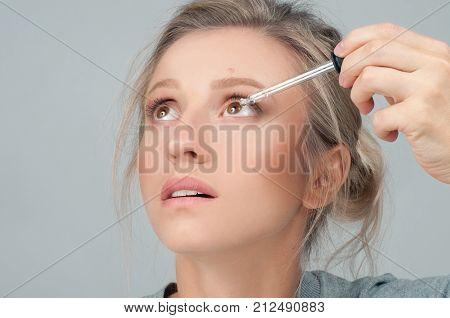 Closeup Of Beautiful Woman Applying Eyedrops In Her Eyes