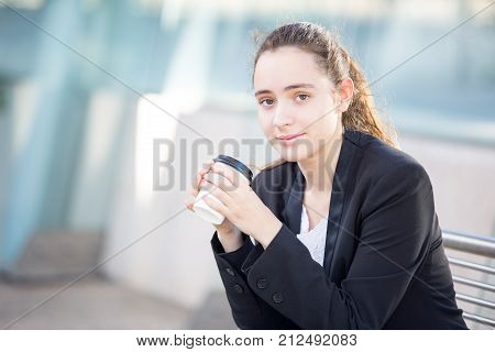 Calm coffee lover enjoying favorite drink outdoors and looking at camera. Attractive manager in jacket holding disposable cup. Beverage for busy people concept