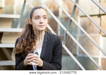 Contemplative business lady looking into distance and dreaming of successful career. Pensive calm student girl enjoying coffee outdoors. Ambitious intern concept