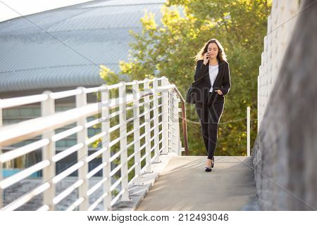Pensive confident young lady having phone conversation while walking over street. Busy female manager in formal suit talking on mobile phone. Going to work concept