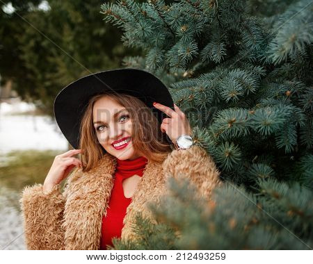 Young attractive girl outdoors in winter. The girl is standing next to the fir-tree.