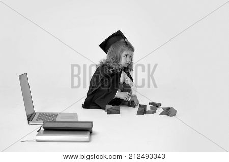 Small boy child with long blond hair in blue shirt black graduation gown and cap sitting and playing with wooden blocks near notebook and diaries isolated on white background