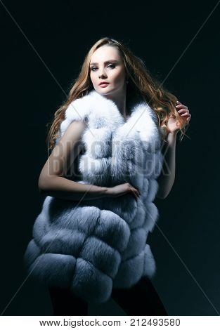 Woman In Fur Vest On Grey Background