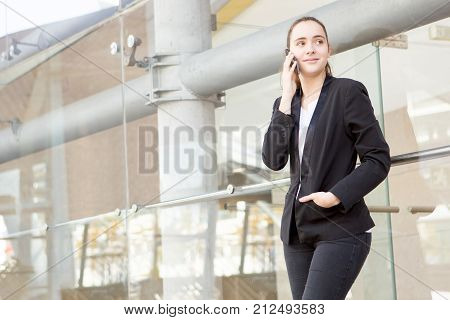 Serious female business specialist calling client while walking over city street. Confident attractive businesswoman working out of office. Mobile business concept