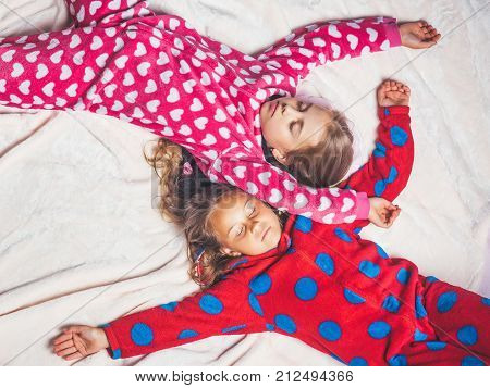 Girls in pajamas sleep in bed top view. Good night napping bedtime slumber dream sleepover concept poster