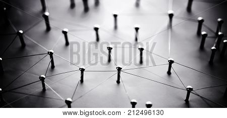 Linking entities. Network, networking, social media, connectivity, internet communication abstract. Web of thin silver wires on white background. Shallow depth of field. Stong shadows. Wide format.