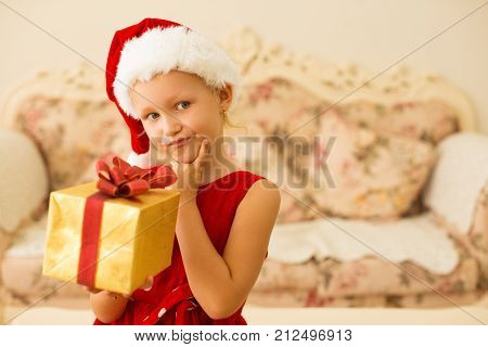 Confused little girl reflecting about Christmas present in living room. Pensive cute kid in santa hat looking away and holding gift box. Anticipation concept