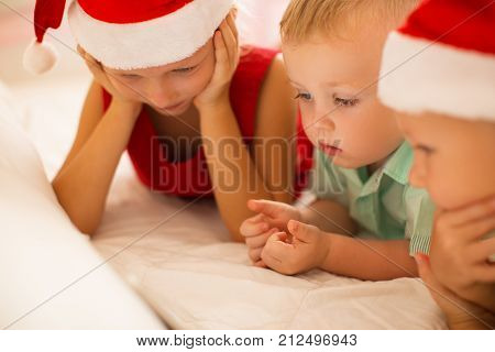 Curious kids watching Christmas movie on device while lying in bed. Concentrated siblings interested in cartoon. Modern childhood concept