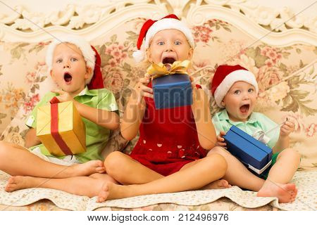 Excited funny children in anticipation of gifts trying to eat Christmas presents. Surprised siblings in Santa hat looking at camera and sitting on sofa. Celebration concept