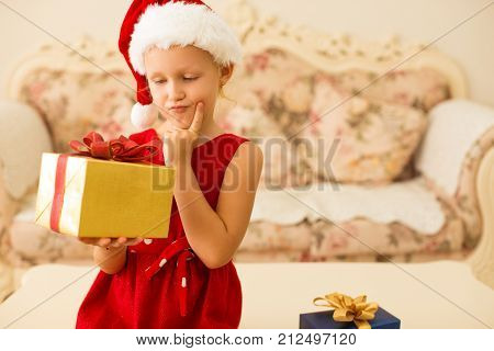 Pensive cute girl in Holiday outfit thinking of Christmas gift anticipating perfect present. Funny kid in Santa hat guessing what is in box. Winter holiday concept