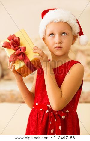 Pensive girl in Santa hat shaking Christmas present. Misunderstanding thoughtful kid dreaming of perfect gift and looking up. Winter holiday concept