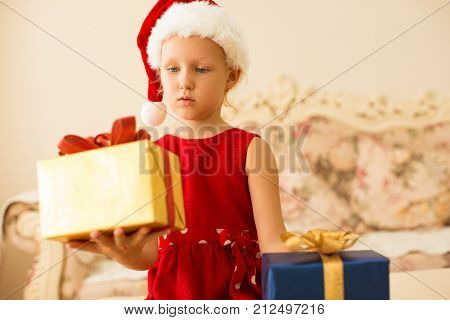 Thoughtful girl choosing New Years gift and holding presents. Uncertain kid in Santa hat weighting gift boxes at home. Choice concept