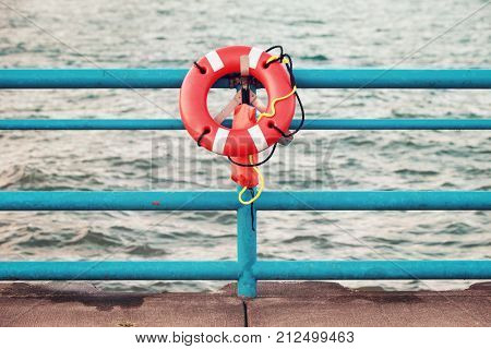 Life ring hanging on the pier railing at the sea