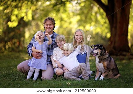A portrait of a family of 5 blonde haired caucasian people sitting outside under the trees with their adopted pet German Shepherd Mix Breed Dog.