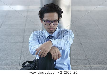 Unemployed young Asian businessman sitting on the floor of sidewalk office. Depressed unemployment business concept.