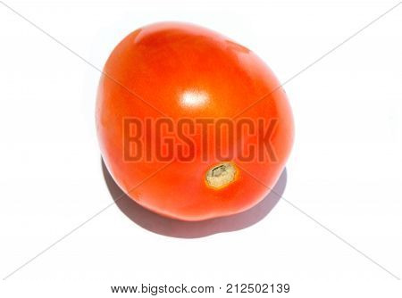One red tomato on white background. Fresh red tomato closeup. Tomato on table closeup photo. Fresh vegetable for salad. Tomato for cooking. Raw vegetarian food. Juicy vegetable. Ketchup ingredient