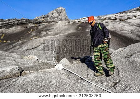 Ranau,Sabah,Borneo-March 13,2016:Climber carefully moving down from Low's Peak to after successfully completed conquering the mountain Kinabalu at Sabah,Malaysia.