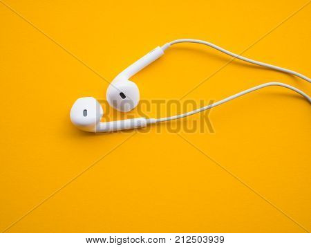 white earphones on a yellow table background