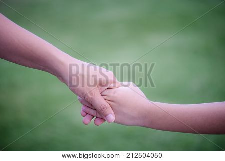 Mother holding a hand of his son with green glass background. Love famiy and mother day concept.