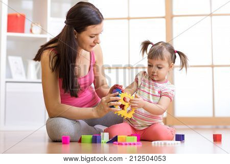 mother and her child girl playing with colorful logical sorter toy