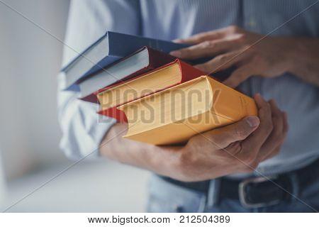 Men's hands hold books