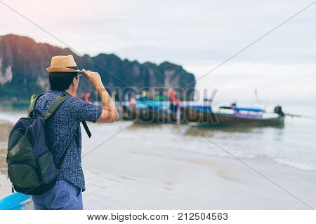 Young man traveler with green backpack and hat looking at the sea with long boat thailand background from Ao Nang Beach Krabi. Traveling in Krabi Thailand Traveler summer concept