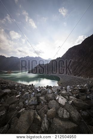 A great outdoor spot near Dubai. A beautiful picnic or camping spot and water reservoir at Hatta, UAE. Reflection on the lake water in the evening light.