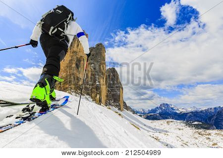 Mountaineer backcountry ski spring walking up along a snowy ridge with skis in the backpack. In background blue cloudy sky and shiny sun and Tre Cime, Drei Zinnen in South Tirol, Dolomites, Italy.