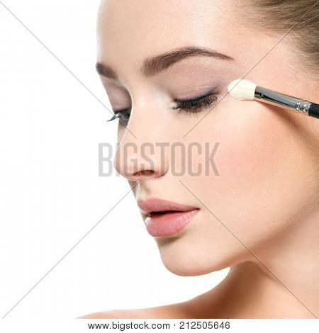 Girl makes makeup. Beautiful woman apply mascara on eyelashes  with cosmetic brush - isolated on white. Woman applies makeup shadow on the eyelid