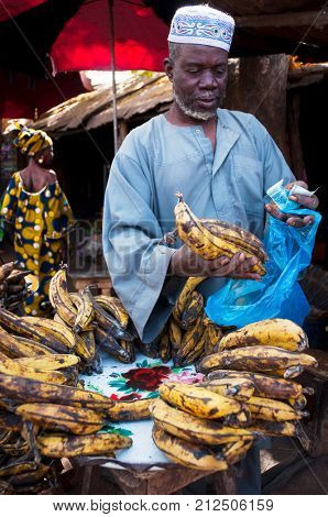 BAMAKO, MALI - CIRCA FEBRUARY 2012: Shopkeeper selling plantain at one of the city's market.