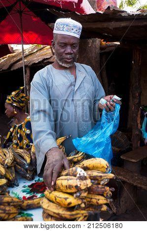 BAMAKO, MALI - CIRCA FEBRUARY 2012: Shopkeeper selling plantain at one of the city's market.