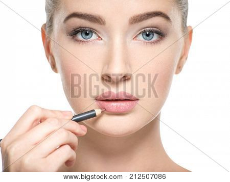 Woman apply lipstick with cosmetic pencil on the lips - isolated on white