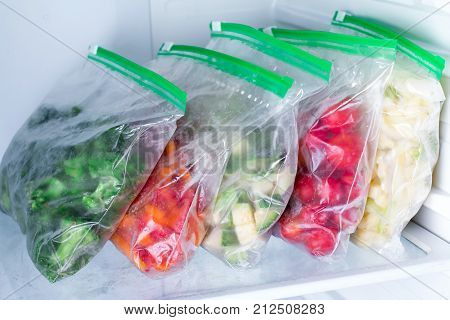 Bags with frozen vegetables in refrigerator. Frozen food