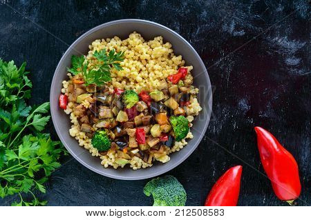 Light healthy dietary vegan dish: couscous and vegetables (zucchini eggplant carrots sweet peppers onions parsley) on a black background. The top view.