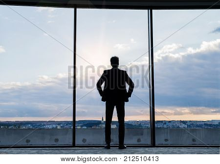 Mature businessman standing at the big windows in a hotel. Man looking at city in the evening. Rear view.
