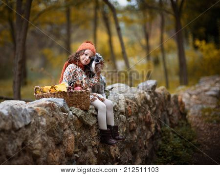 Sad little girl with big dog in the forest in autumn