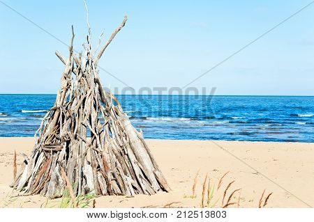 Wigwam Made from wooden branches on the sand of baltic sea beach. Multicolored summertime outdoors horizontal image with blue cloudless sky background.
