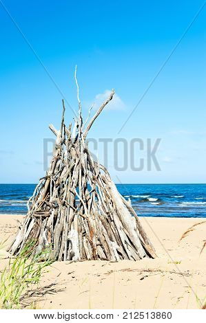 Wigwam Made from wooden branches on the sand of baltic sea beach. Multicolored summertime outdoors vertical image with blue cloudless sky background.