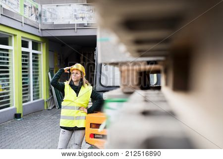 Female forklift truck driver outside a warehouse. A woman standing by the fork lift truck, looking at something.